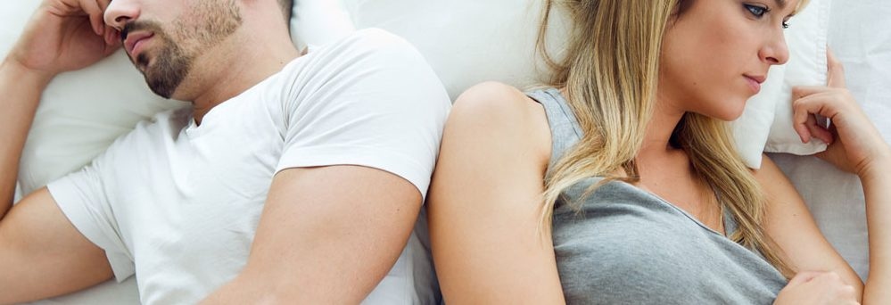 Couple laying in bed not talking to each other to represent Dr. Karen Gless' blogpost Understanding Delayed Ejaculation