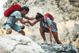 Young couple hiking and climbing at the mountain.