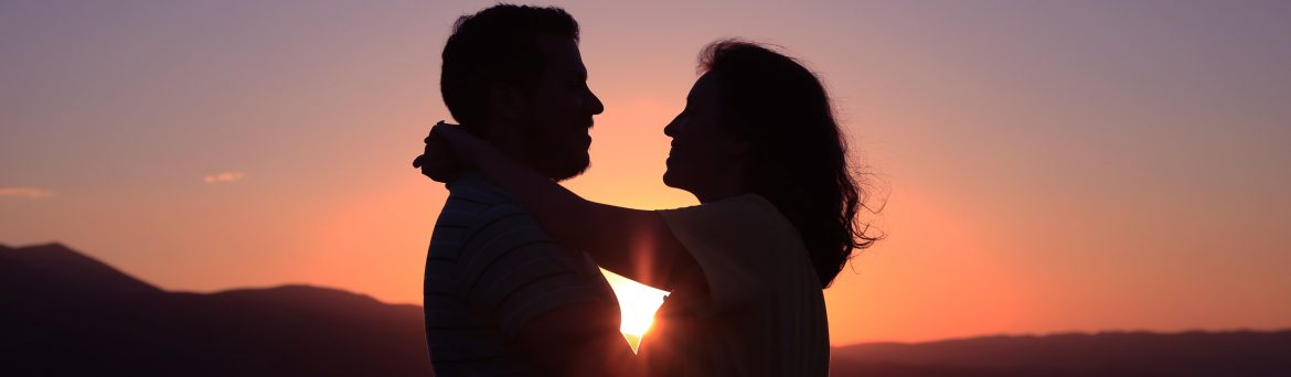 Couple Hugging with the Sunset Between Them